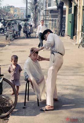 Tháng 12/1968. Em bé cắt tóc trên vỉa hè.